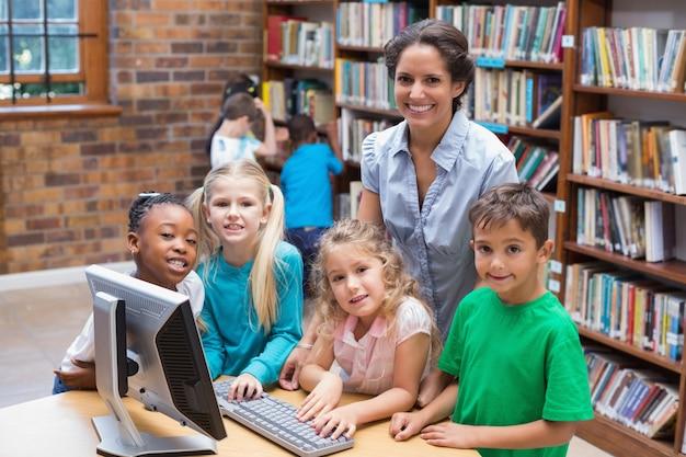 Nette schüler und lehrer, die computer in der bibliothek betrachten
