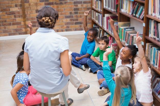Nette schüler und lehrer, die klasse in der bibliothek haben