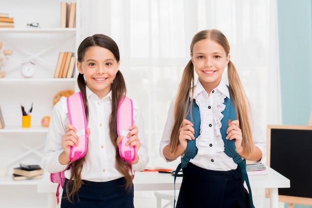 Nette schulmädchen mit den rucksäcken, die im klassenzimmer stehen