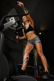 Nette sportliche brünette frau, die unter verwendung der elliptischen kreuztrainermaschine in der dunklen turnhalle mit schwarzen wänden, hohe winkelansicht ausübt