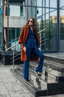 Nette stilvolle frau mit dem gehen in der städtischen stadtgeschäftsstraße gekleidet in warmem braunem mantel und blauem anzug, frühling herbst trendige mode straße stil, sonnenbrille tragend
