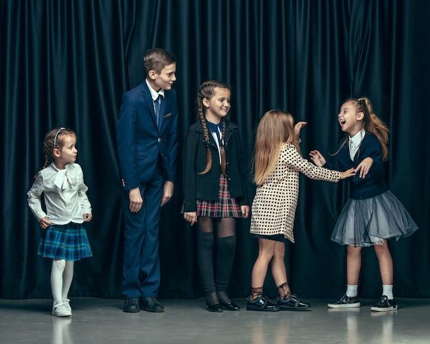 Nette stilvolle kinder auf dunkelheit. schöne jugendlich mädchen und jungen, die zusammen stehen
