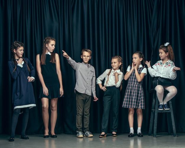 Nette stilvolle kinder auf dunklem studio. die schönen jugendlich mädchen und jungen, die zusammen stehen