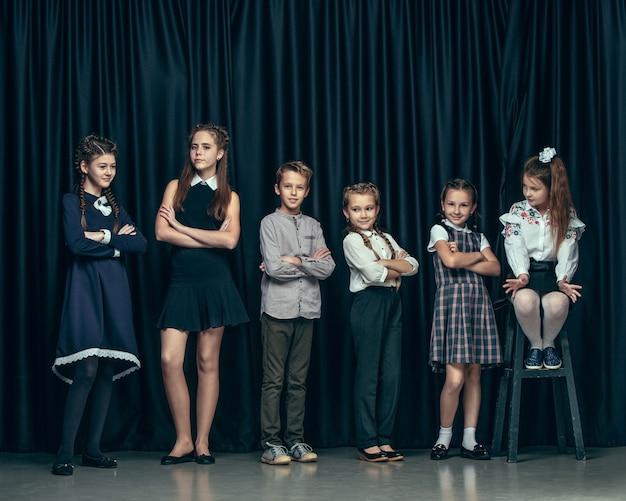 Nette stilvolle kinder auf dunklem studiohintergrund. die schönen jugendlich mädchen und jungen, die zusammen stehen