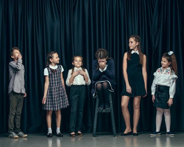 Nette stilvolle kinder auf dunkler studiowand. die schönen jugendlich mädchen und ein junge, die zusammen stehen