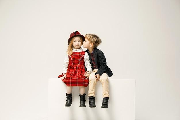 Nette stilvolle kinder auf weißer wand