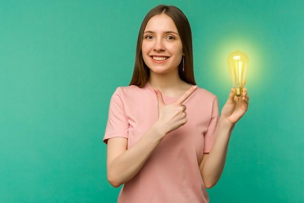 Nette studentin, die auf die lampe in ihrer hand auf einem zeigt. das konzept einer idee oder einer kreativen einsicht.