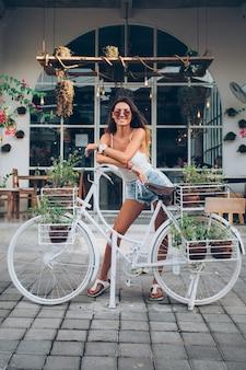 Nette tätowierte kaukasische frau in jeansshorts und weißem oberteil steht durch fahrrad auf hintergrund des straßencafés.