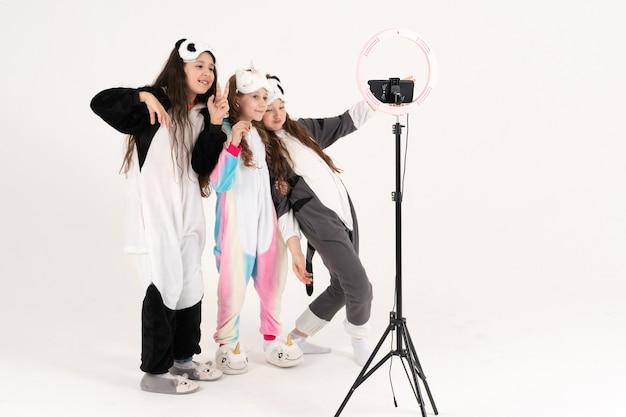 Nette teenager-mädchen in kigurumi und schlafmasken lächeln und schießen ein video. weltkindertag
