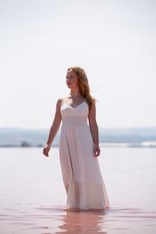Nette teenagerfrau, die weißes kleid steht, das auf einem erstaunlichen rosa see steht