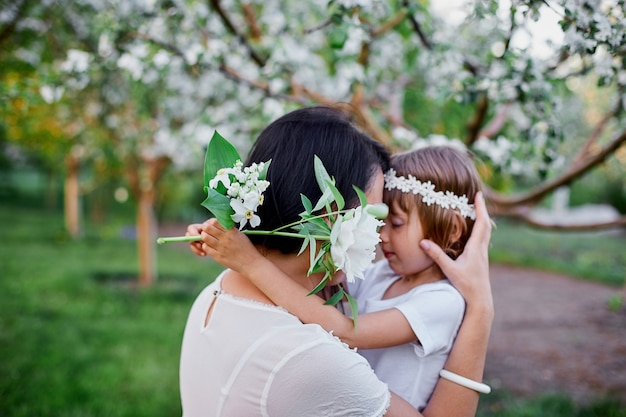 Nette tochter und mutter, die im blühenden frühlingsgarten umarmen glückliche frau und kind, weiße kleidung im freien tragend, frühlingssaison kommt. muttertagsferienkonzept