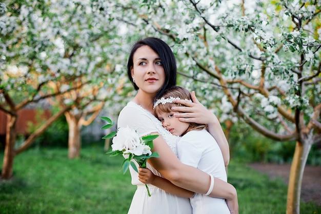 Nette tochter und mutter, die im blühenden frühlingsgarten umarmen