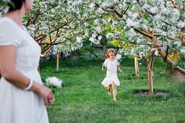Nette tochter und mutter im blühenden frühlingsgarten