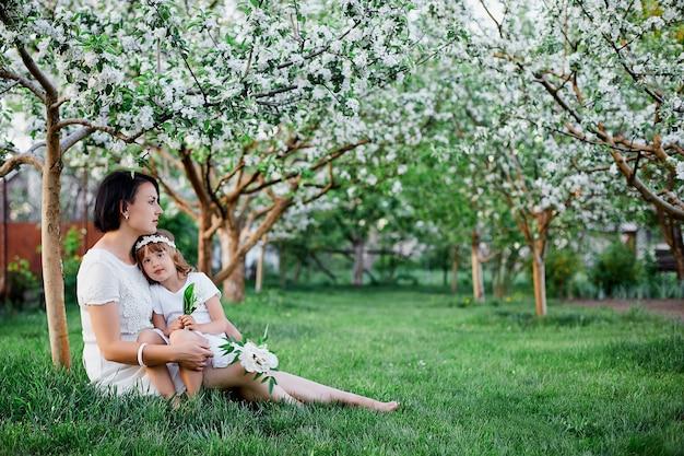 Nette tochter und mutter sitzen und umarmen im blühenden frühlingsgarten
