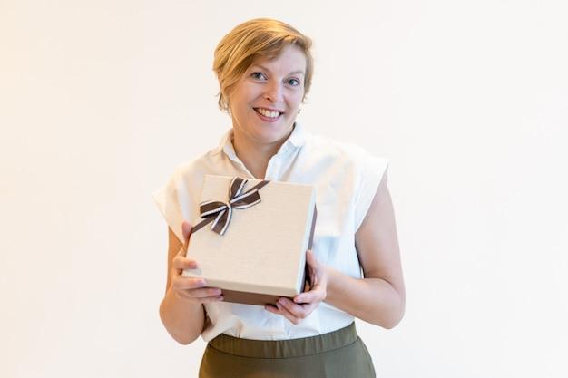 Nette überzeugte reife geschäftsfrau, die geschenkbox hält