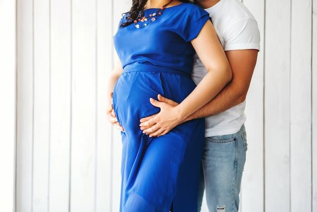 Nette umarmung der schwangeren frau mit ihrem ehemann