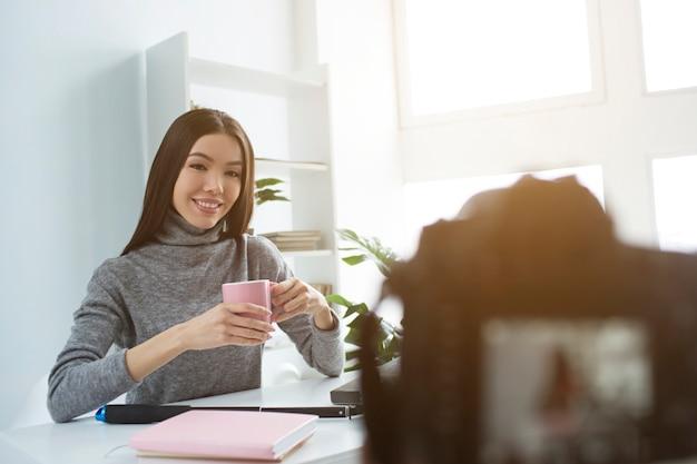 Nette und attraktive frau sitzt am tisch und trinkt tee von der rosa schale
