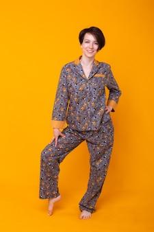 Nette und fröhliche frau im haus trägt pyjama in der gelben wand