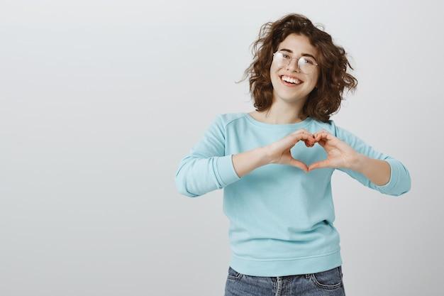 Nette und glückliche lächelnde frau, die herzgeste über brust zeigt