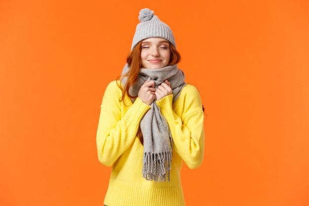 Nette und glückliche rothaarige frau, die entlang des winterferienmarktes geht, schließen augen
