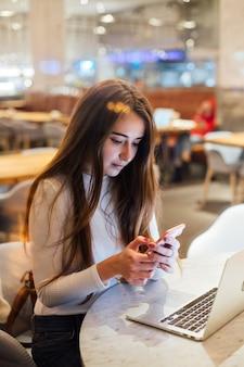 Nette und hübsche junge frau auf smartphone im café