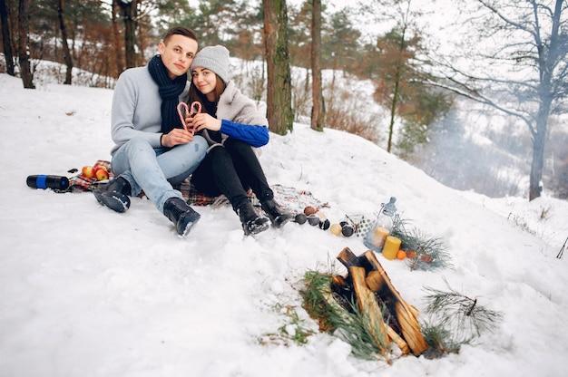 Nette und liebevolle paare in einem winterwald