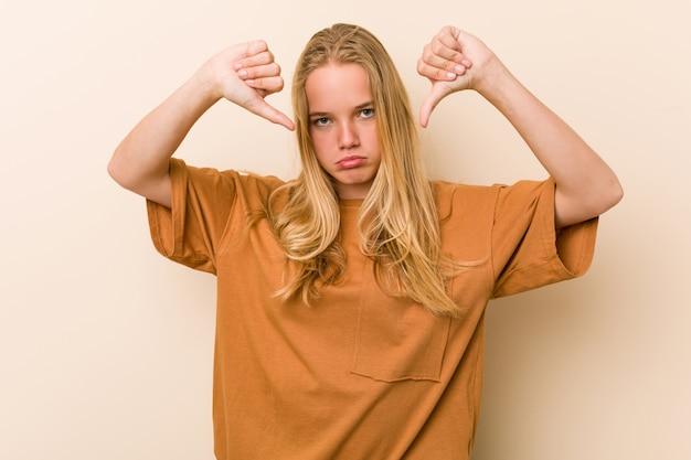Nette und natürliche jugendlichfrau, die unten daumen zeigt und abneigung ausdrückt.