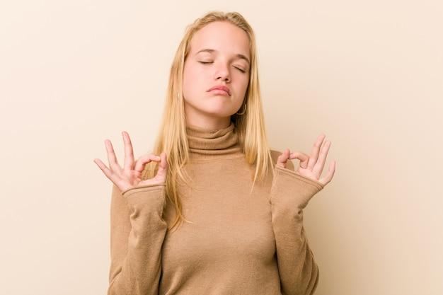 Nette und natürliche jugendlichfrau entspannt sich nach hartem arbeitstag, sie führt yoga durch.