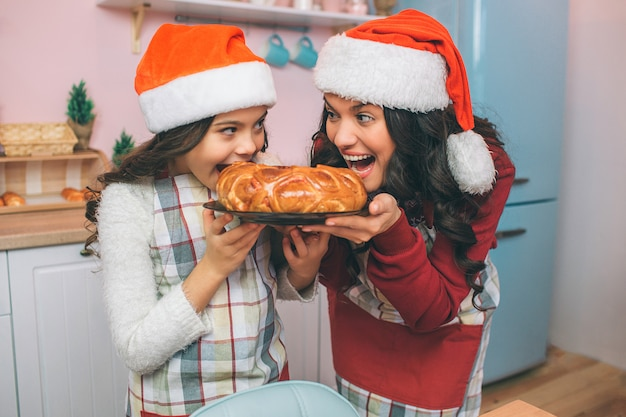 Nette und positive junge frau und mädchen halten platte mit torte und betrachten einander. sie beißen es. frau und mädchen lächeln. sie tragen schürzen und weihnachtsmützen.