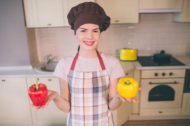 Nette und schöne frau steht in der küche. sie hält rote und gelbe paprikaschoten. mädchen lächelt. sie sieht glücklich aus. junge frau trägt pron.