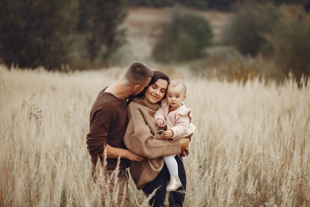 Nette und stilvolle familie, die auf einem gebiet spielt