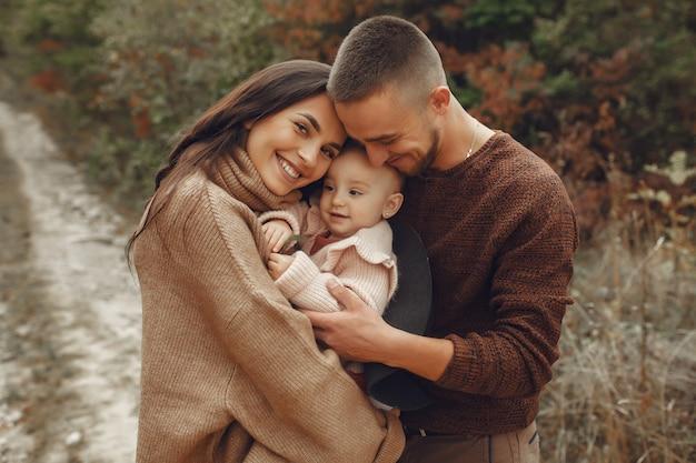 Nette und stilvolle familie, die auf einem herbstgebiet spielt