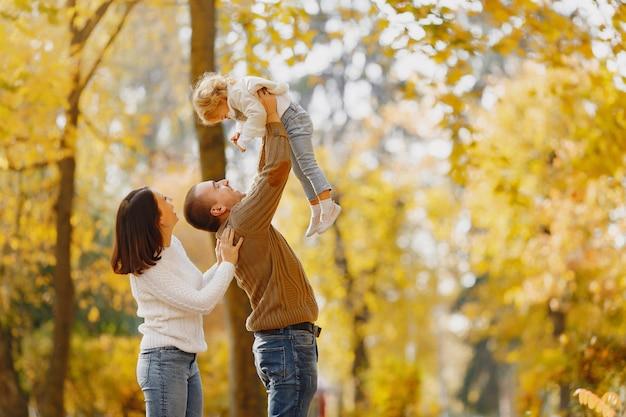 Nette und stilvolle familie, die in einem herbstfeld spielt