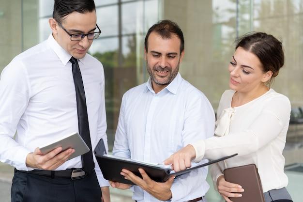 Nette unternehmensleiter, die diagramm im ordner analysieren