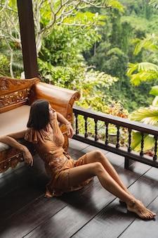 Nette weibliche person, die sich auf dem sofa lehnt, während sie auf holzboden im bungalow sitzt und tropisches klima genießt