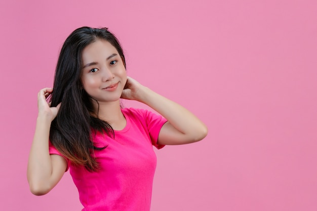 Nette weiße asiatische frau wirft sich mit einem rosa haar auf einem rosa auf.