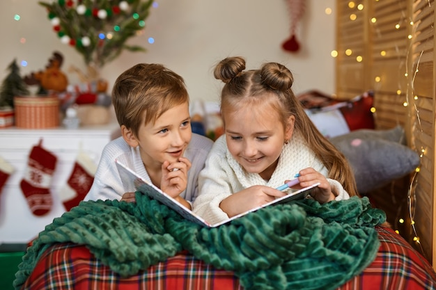 Nette zwei glückliche kinder, die einen brief an den weihnachtsmann schreiben