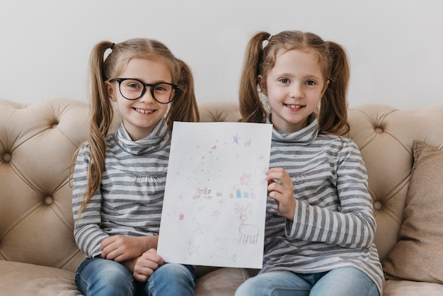 Nette zwillinge, die eine zeichnung halten