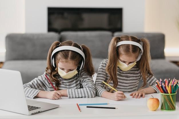 Nette zwillinge, die innen medizinische masken tragen