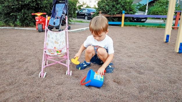 Netter 3 jahre alter kleiner junge, der auf dem kinderspielplatz im park spielt. kleinkind gräbt sand mit schaufeln