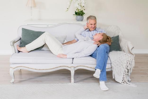 Netter älterer mann und frau der vorderansicht auf einer couch