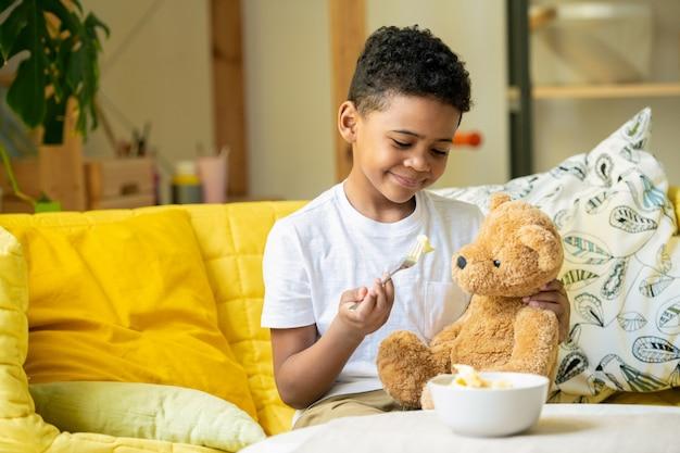Netter afrikanischer kleiner junge, der hand winkt und gelbe sprechblase mit begrüßung zeigt, während auf dem boden durch weißes zelt im wohnzimmer sitzend
