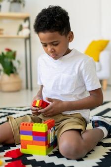 Netter afrikanischer vorschulkind in der freizeitkleidung, die auf dem boden im kindergarten spielt und haus aus mehrfarbigen plastikdetails baut