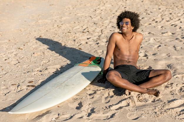 Netter afroamerikanermann, der auf sand mit surfbrett sitzt
