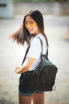 Netter asiatischer jugendlicher mit dem moderucksack, der im freien steht