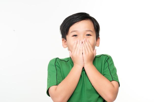 Netter asiatischer junge bedeckt seinen mund mit seinen händen.