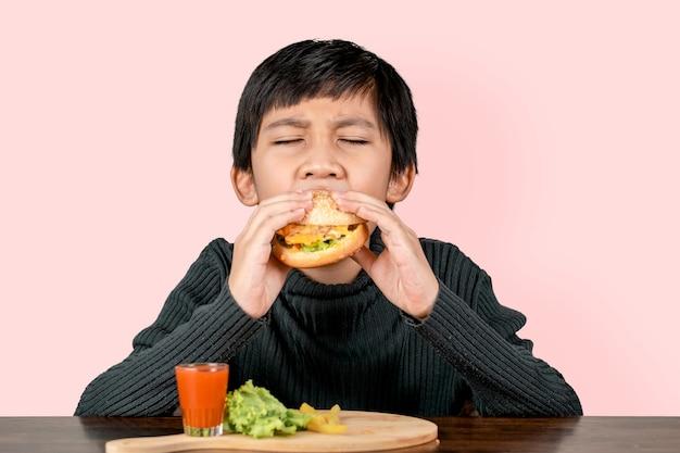 Netter asiatischer junge, der mit glück einen köstlichen hamburger isst