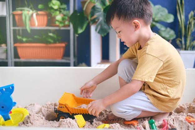 Netter asiatischer junge, der mit sand allein spielt kind, das mit sandspielzeug im städtischen hausgarten spielt