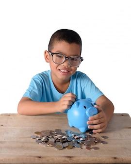 Netter asiatischer junge, der münzen in das sparschwein lokalisiert auf weißem hintergrund steckt