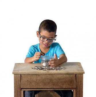 Netter asiatischer junge, der münzen in die glasschüssel lokalisiert auf weiß steckt